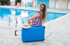 Travel, summer holidays and vacation concept - Beautiful woman near pool area with luggage. Stock Photography