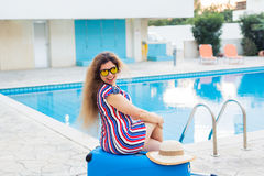 Travel, summer holidays and vacation concept - Beautiful woman near pool area with luggage. Royalty Free Stock Images