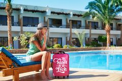 Travel, summer holidays and vacation concept - Beautiful woman walking near hotel pool area with red suitcase in Egypt.  stock image