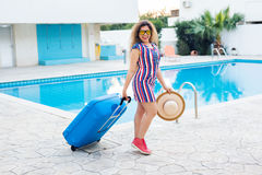 Travel, summer holidays and vacation concept - Beautiful woman walking near pool area with luggage. Stock Photo