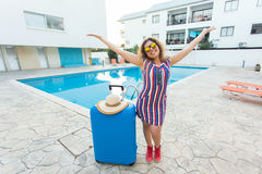 Travel, summer holidays and vacation concept - Happy woman near pool area with luggage. Stock Images