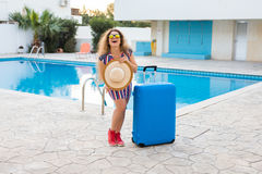 Travel, summer holidays and vacation concept - Happy woman near pool area with luggage. Stock Photo