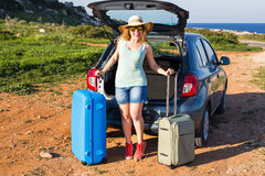 Travel, summer holidays and vacation concept - Young woman with suitcases on car trip. Royalty Free Stock Image