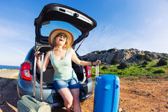 Travel, summer holidays and vacation concept - Young woman with suitcases on car trip. Royalty Free Stock Photos