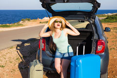 Travel, summer holidays and vacation concept - Young woman with suitcases on car trip. Royalty Free Stock Images