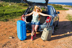 Travel, summer holidays and vacation concept - Young woman with suitcases on car trip. Stock Photos