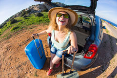 Travel, summer holidays and vacation concept - Young woman with suitcases on car trip. Stock Image