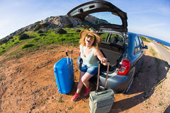 Travel, summer holidays and vacation concept - Young woman with suitcases on car trip. Royalty Free Stock Photography