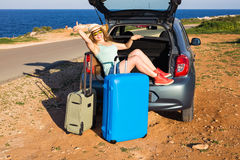 Travel, summer holidays and vacation concept - Young woman with suitcases on car trip. She is sitting in car back and Stock Image