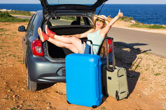 Travel, summer holidays and vacation concept - Young woman with suitcases on car trip. She is sitting in car back and Royalty Free Stock Photos
