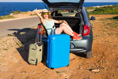 Travel, summer holidays and vacation concept - Young woman with suitcases on car trip. She is sitting in car back and Royalty Free Stock Photography