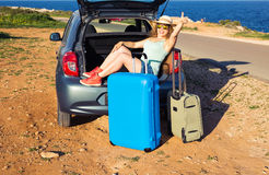 Travel, summer holidays and vacation concept - Young woman with suitcases on car trip. She is sitting in car back and Royalty Free Stock Images