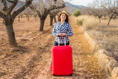 Travel, summer and people concept - woman with red suitcase in hat over the nature background. She is on holiday stock images