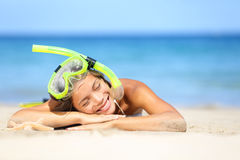 Travel summer vacation beach woman with snorkel. Smiling beautiful young woman relaxing lying on white beach sand in the summer sun with a blue ocean. Photo Stock Image