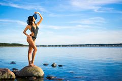 Travel and summer vacation concept - slim beautiful woman in bik. Travel and summer vacation concept - young slim beautiful woman in bikini posing on the beach Stock Photos