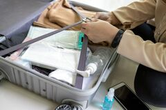 Free Travel,summer Vacation,new Normal,hands Of Asian Woman Preparing The Luggage,medical Face Mask,hand Sanitizer Gel In Suitcase For Royalty Free Stock Images - 185767209