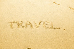 Travel text written on sand Stock Photos
