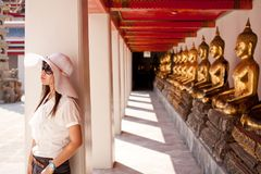 Travel in Thai temple. Smiling young thai girl and white hat travel in temple thai Stock Photography