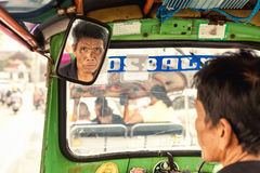 Travel in Thailand: Asian man, driver tuk tuk carefully looks in the rearview mirror on travelling tourist Royalty Free Stock Photos