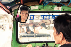 Travel in Thailand: Asian man, driver tuk tuk carefully looks in the rearview mirror on travelling tourist Stock Image