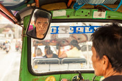 Travel in Thailand: Asian man, driver tuk tuk carefully looks in the rearview mirror on travelling tourist Stock Photo