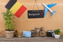 Blackboard with text & x22;Belgium& x22;, flag of the Belgium, airplane model, little bicycle and suitcase, camera, compass. Travel time - blackboard with text royalty free stock photography