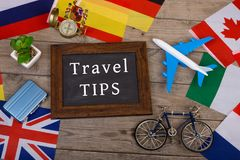 Blackboard with text & x22;Travel TIPS& x22;, flags of different countries, airplane model, little bicycle and suitcase, com. Travel time - blackboard with text Stock Image