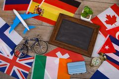 Travel time - blank blackboard, flags of different countries, airplane model, little bicycle and suitcase, compass. On wooden background Stock Photos