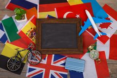 Travel time - blank blackboard, flags of different countries, airplane model, little bicycle and suitcase, compass. On wooden background Stock Image