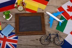 Travel time - blank blackboard, flags of different countries, airplane model, little bicycle and suitcase, compass. On wooden background Stock Images