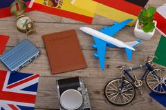 Travel time - passport, camera, flags of different countries, airplane model, little bicycle and suitcase, compass. On wooden background Royalty Free Stock Photos