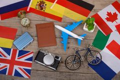 Travel time - passport, camera, flags of different countries, airplane model, little bicycle and suitcase, compass. On wooden background Stock Image