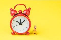 Travel time, reminder for airline checkin for traveller concept, miniature people young lady with luggages or baggage standing. With red alarm clock on solid royalty free stock images