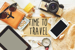 travel. time to travel concept text sign on card. summer planning vacation, flat lay. tablet, camera sunglasses compass passport