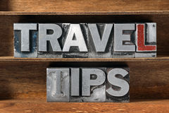 Travel tips tray. Travel tips phrase made from metallic letterpress type on wooden tray Royalty Free Stock Image
