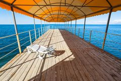 One plastic sunbed in outdoor solarium over sea Royalty Free Stock Image