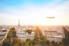 Travel to France, airplane flying over beautiful panoramic cityscape of Paris royalty free stock photography