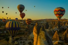 Travel to Goreme, Cappadocia, Turkey. The sunrise in the mountains with a lot of air hot balloons in the sky. Early morning - entertainment for tourists stock photography