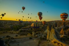 Travel to Goreme, Cappadocia, Turkey. The sunrise in the mountains with a lot of air hot balloons in the sky. Early morning - entertainment for tourists royalty free stock photography