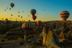 Travel to Goreme, Cappadocia, Turkey. The sunrise in the mountains with a lot of air hot balloons in the sky. Early morning - entertainment for tourists royalty free stock image