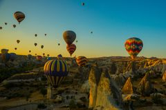 Travel to Goreme, Cappadocia, Turkey. The sunrise in the mountains with a lot of air hot balloons in the sky. Early morning - entertainment for tourists stock photo