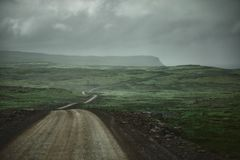 A mountain road to the town of Isafjordur and a view of the fjord. Travel to Iceland. A mountain road with fog to the town of Isafjordur and a view of the fjord Stock Photos