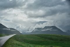 A mountain road to the town of Isafjordur and a view of the fjord. Travel to Iceland. A mountain road with fog to the town of Isafjordur and a view of the fjord Royalty Free Stock Photos