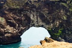 Natural arch in Dyrholaey cliff in Iceland. Travel to Iceland - natural arch in Dyrholaey cliff near Vik I Myrdal village on Atlantic South Coast in Katla Royalty Free Stock Photography