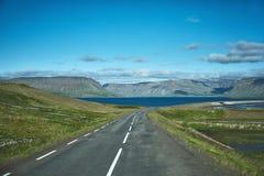 Plot of asphalt road in a bright sunny mountain landscape. Travel to Iceland. plot of asphalt road in a bright sunny mountain landscape. focus on the road Stock Photo
