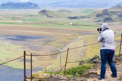 Tourist takes photo of ocean coast in Iceland. Travel to Iceland - tourist takes photo of Solheimafjara coast from Dyrholaey promontory near Vik I Myrdal village stock photo