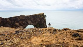 View of lava arch on Dyrholaey cape in Iceland. Travel to Iceland - view of lava arch on Dyrholaey cape, near Vik I Myrdal village on Atlantic South Coast in royalty free stock photos