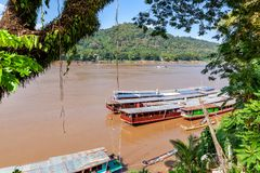 Travel to Laos, Southeast Asia, view of the famous Asian Mekong River, traditional long Laotian boats. Beautiful landscape and. Popular travel destination stock photos