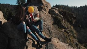 Travel to the mountains. Beautiful couple in love sits on the rock and learns a map. They talk with each other, laughing stock video