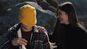 Travel to the mountains. Beautiful couple in love sits on the rock and learns a map. They talk with each other, laughing stock footage
